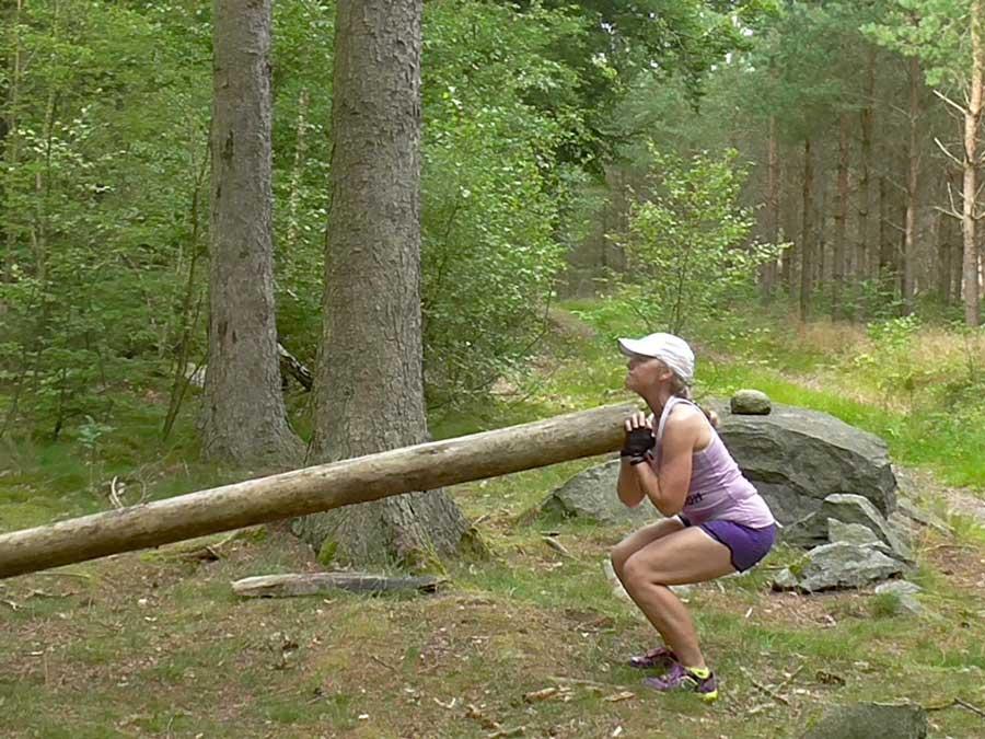 Knäböj med stor stock i skogen